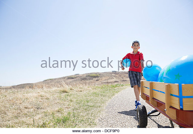 Little boy with cart full of balloons walking on pathway - Stock Image
