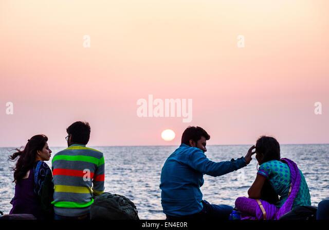 Mumbai India Asian Churchgate Marine Drive Back Bay Arabian Sea man woman couple romantic friends sunset water - Stock Image