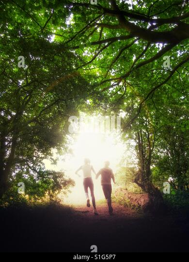 Two children running out of dark wood into the bright unknown - Stock-Bilder