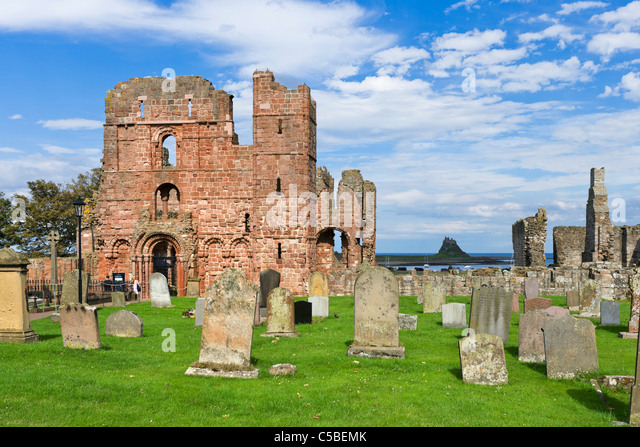 Graveyard at Lindisfarne Priory with Lindisfarne Castle in the distance, Holy Island, Northumberland, North East - Stock Image