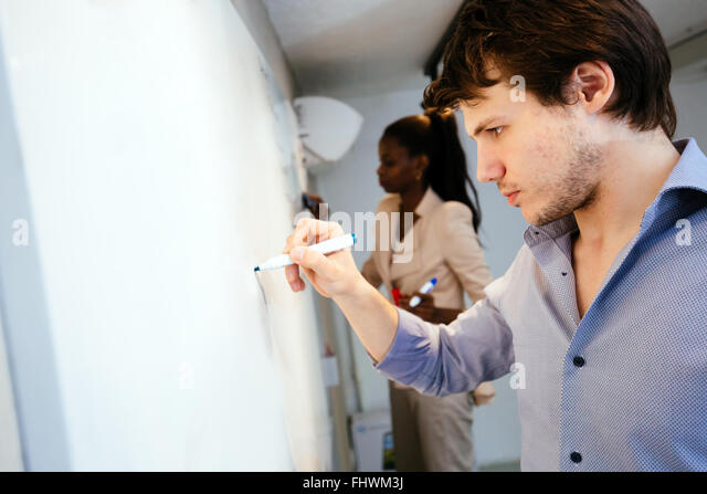Smart people writing on whiteboard in search of a solution - Stock Image
