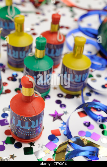 A still life image of colourful confetti, blue streamer and party poppers on white background - Stock Image