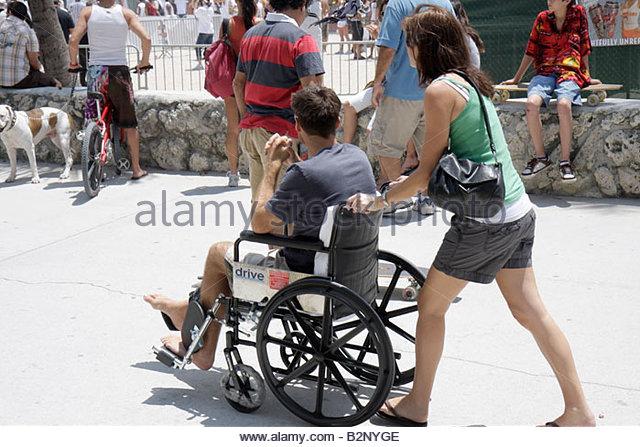 Miami Beach Florida Ocean Drive Lummus Park man woman couple wheelchair disabled push - Stock Image