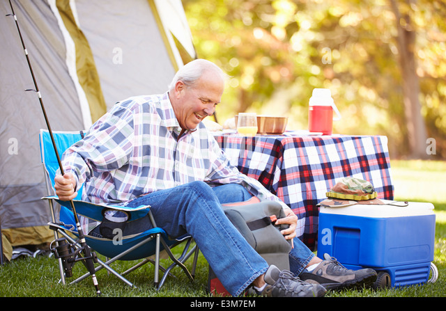Senior Man On Camping Holiday With Fishing Rod - Stock Image