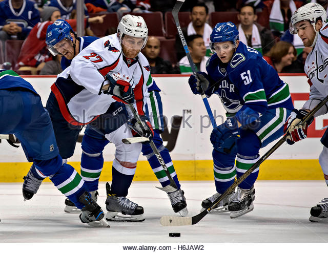 Vancouver. 30th Oct, 2016. Washington Capitals' Karl Alzner (Front, L) competes for the puck with Vancouver - Stock-Bilder
