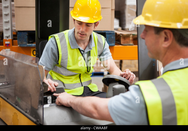 Men with machinery in warehouse - Stock Image