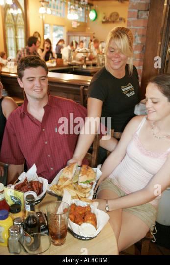 Toledo Ohio The Blarney Irish Pub and Restaurant waitress serves food couple man woman - Stock Image