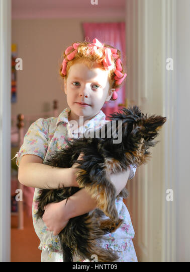 A little girl in rollers holding her dog - Stock Image