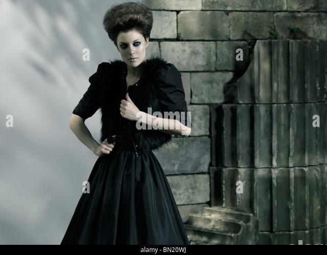 High fashion photo of a beautiful woman wearing long black dress - Stock Image