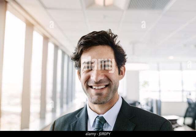 Portrait of successful young businessman standing in office. Manager in suit looking at camera with a smile. - Stock Image