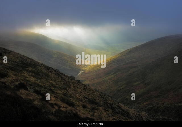 A shaft of light through moody skies over  Crowden Brook Kinder Scout  and the Vale of Edale, Peak District, Derbyshire, - Stock Image