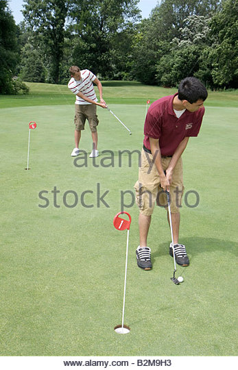 Wisconsin Kenosha Kansasville Brighton Dale Links golf course county park system practice green boy teen boy putter - Stock Image