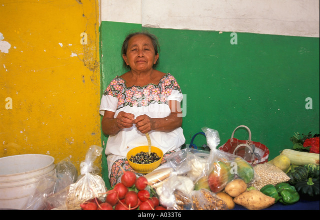 Mexico maya woman at market mayan produce vegetables tomatoes yucatan colorful wall colorful costume traditional - Stock Image