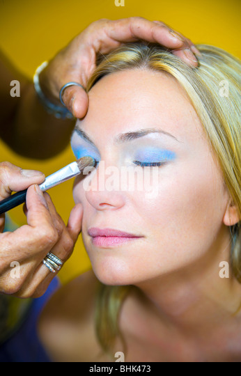 Makeup artist applying eyeshadow on a young woman with eyes closed - Stock Image