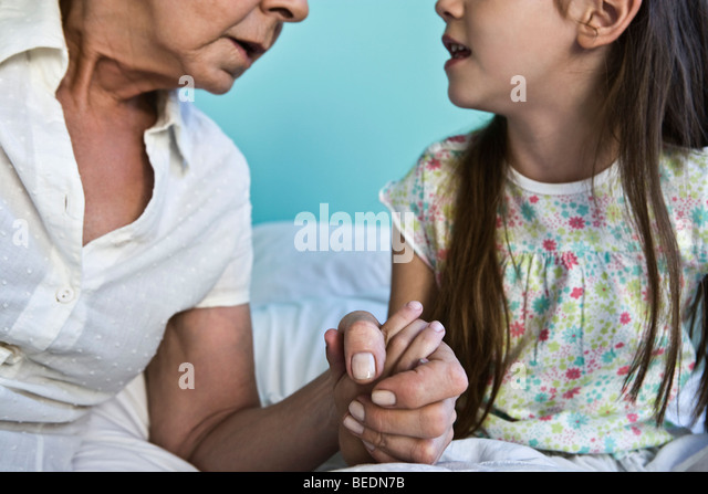 Grandmother and young granddaughter holding hands and talking, cropped - Stock-Bilder