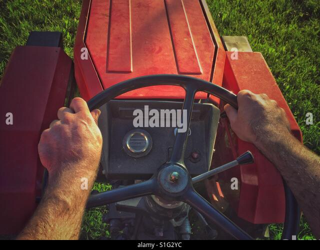 Hands of a man on steering wheel driving tractor - Stock-Bilder