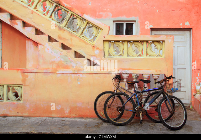 bicycles on grunge tropical Caribbean orange yellow facade Mexico - Stock Image