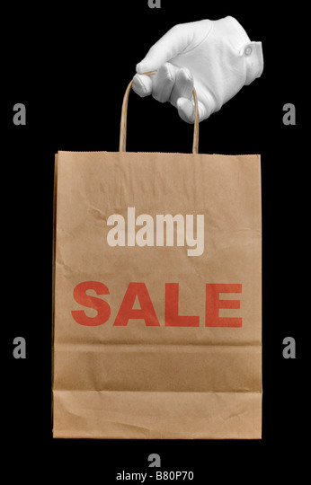 Hand in a white glove holding a brown recycled paper shopping bag with the word SALE written on it isolated on black - Stock Image