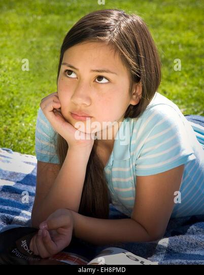 Teenage Vietnamese/Caucasian girl 11-13 year olds laying on stomach on grass meditating, MR  © Myrleen Pearson - Stock-Bilder