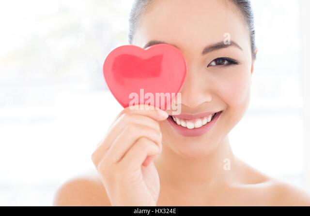MODEL RELEASED. Young Asian woman covering eye with heart, portrait. - Stock-Bilder