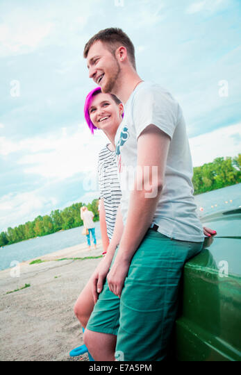 Man and woman sitting on an upturned boat - Stock-Bilder