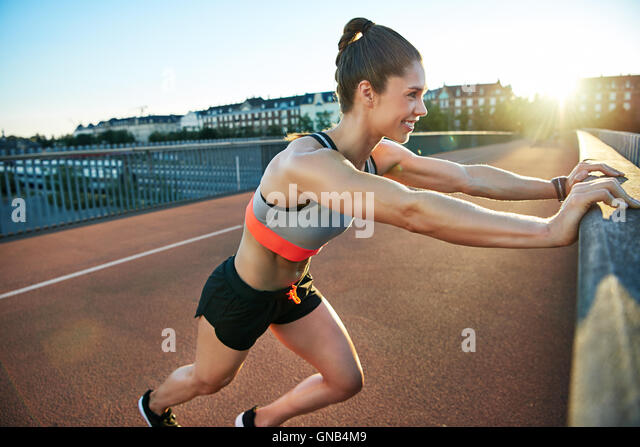 Woman stretches her legs by pressing against bridge by pressing against bridge - Stock Image