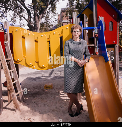 Middle-aged woman leaning on slide at playground - Stock Image