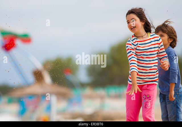 Boy and girl throwing sand on the beach - Stock Image