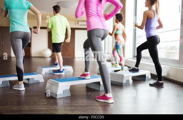close up of people working out with steppers in gym - Stock Image