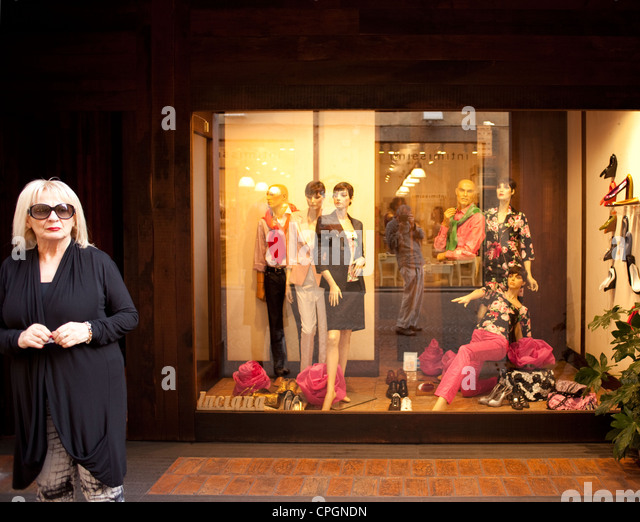 A woman stands in front of her clothing store in Orvieto, Italy. - Stock Image