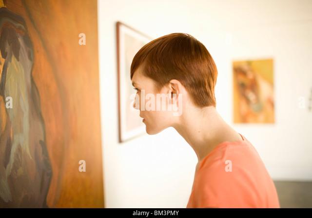 Woman in art museum looking at painting - Stock-Bilder