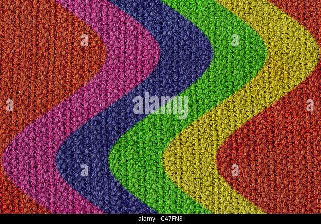 A texture background of a woven wool texture with curving colored strips. - Stock Image