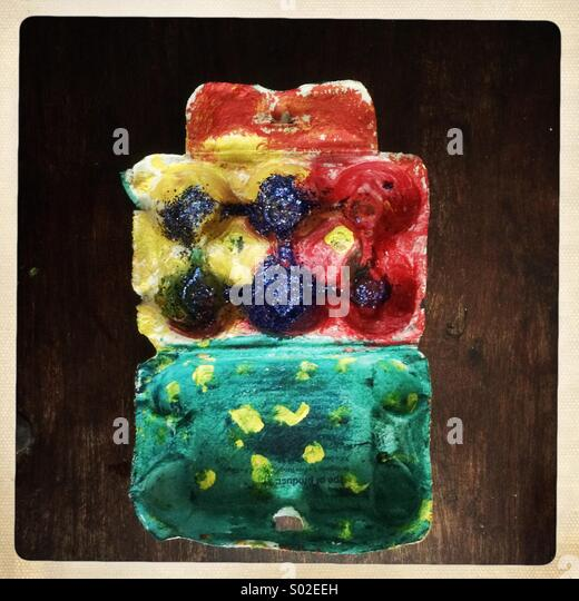Egg box painted colourfully and sprinkled with glitter by a child - Stock Image
