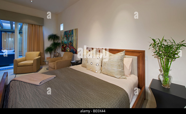 Contemporary teakwood bed with elegant bed linens and upholstered chairs in background by window of bedroom - Stock-Bilder