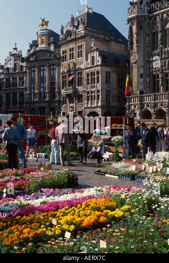 Belgium Brussels Grand Place Grote Markt Sunday flower market shoppers buildings architecture - Stock Image