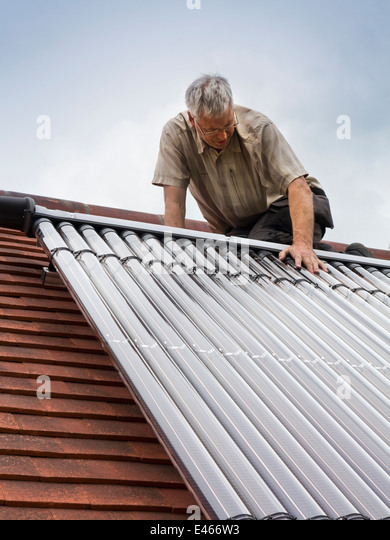 self building house, man fitting Veissmann Solar Thermal Hot Water tubes to south facing roof - Stock Image