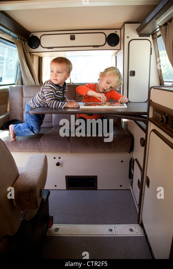 Two brothers are playing in their camper trailer. - Stock Image
