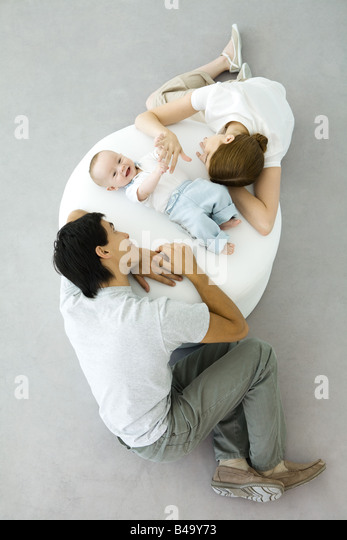 Parents and baby relaxing on ottoman, baby holding mother's hand, overhead view - Stock-Bilder