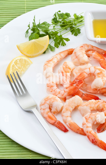 Prawns with lemon slices on plate. - Stock-Bilder