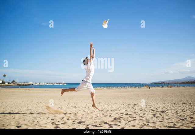 Boy jumping and throwing hat mid air on beach - Stock Image
