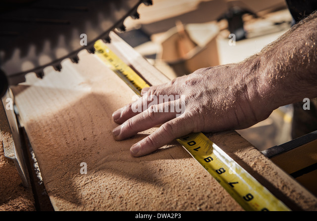 Close up of male carpenter using tape measure in workshop - Stock Image