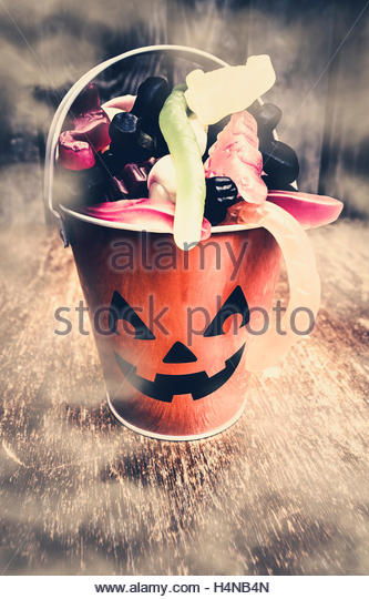 Twilight halloween scene of a pumpkin head holding sweet candies in mysterious shrouds of fog and mist - Stock Image