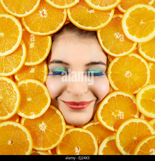 Beautiful woman expression face with orange slice frame - Stock Image