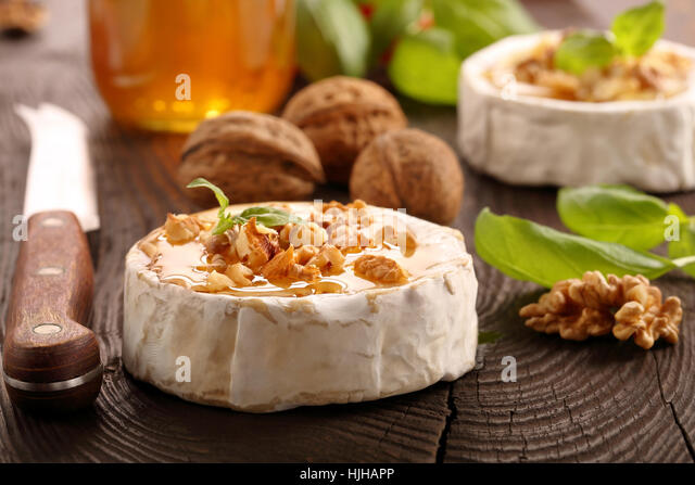 Grilled brie cheese with honey and nuts on old wooden background - Stock Image