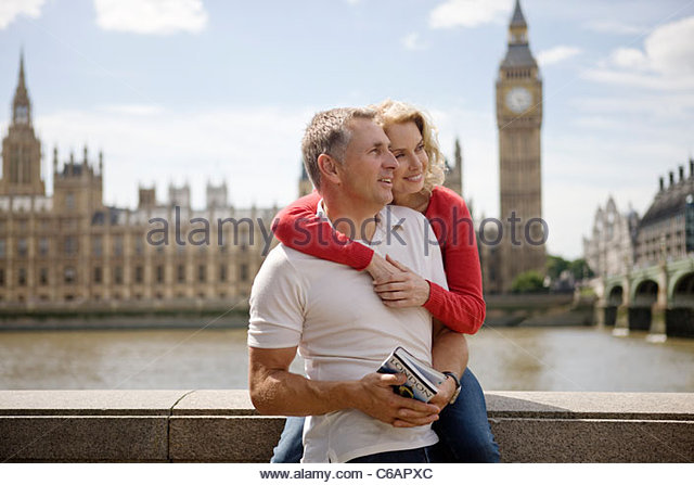 A middle-aged couple in front of the Houses of Parliament, holding a guidebook - Stock Image
