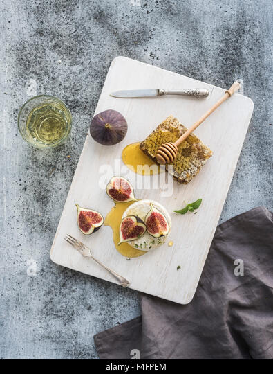 Camembert cheese with fresh figs, honeycomb and glass of white wine on serving board over grunge rustic grey backdrop, - Stock Image