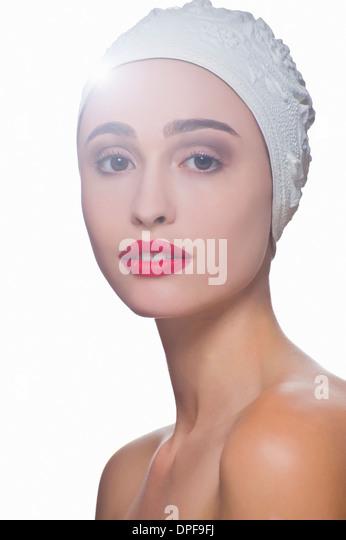 Studio portrait of young woman wearing bathing cap - Stock Image
