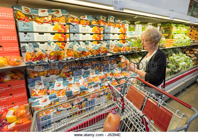 mature woman shopping in costco warehouse supermarket looking at fresh