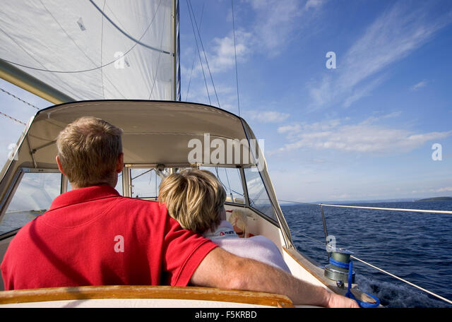 Sweden, Bohuslan, Reare view of sailing couple - Stock Image