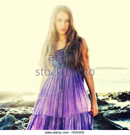 portrait of a young girl wearing a long purple dress on the beach - Stock Image